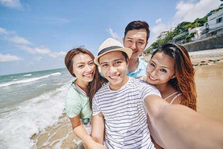 Aziatische smling jongeren nemen selfie op het strand