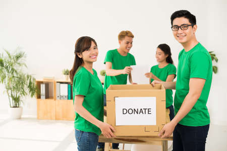 Young Asian volunteers holding cardboard box with donate inscription Stock Photo
