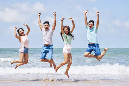 Four cheerful Vietnamese young people jumping on beach