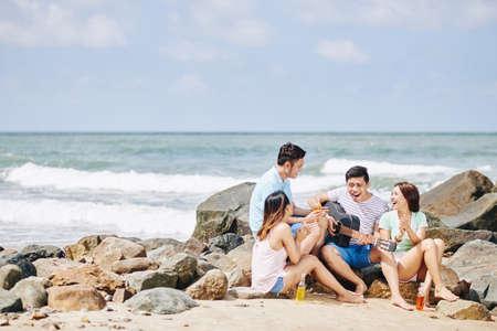 Groep jonge Vietnamese mensen die op kust zitten