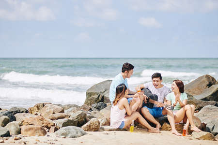 Group of young Vietnamese people sitting on seashore