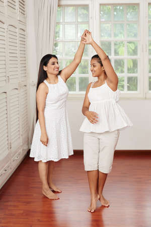 Indian woman and her teenage daughter dancing at home