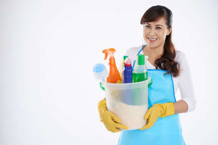 Asian mature woman holding a bucket with detergents and sprays Stock Photo