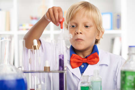 pipeta: Concentrated smart schoolboy working in chemical laboratory