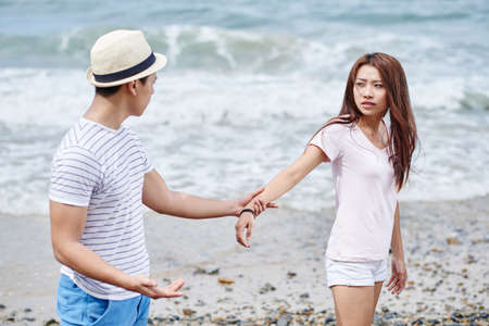 Asian young couple fighting on the beach