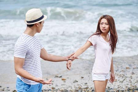 Aziatisch jong paar die op het strand vechten