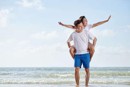 Handsome Vietnamese man giving piggyback ride to his girlfriend