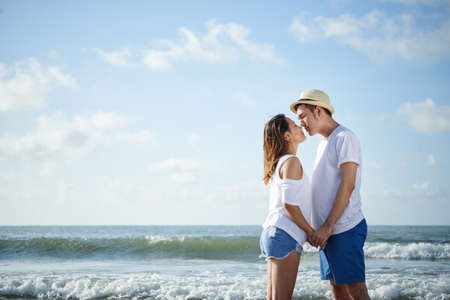 Young Vietnamese couple kissing on the beach Stock Photo