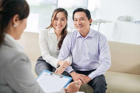 accommodation broker: Asian family talking to estate broker at meeting