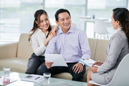 accommodation broker: Vietnamese smiling couple having meeting with real estate