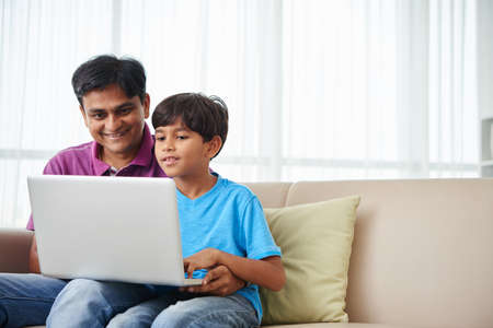 Cheerful Indian kid and his father working on laptop at home