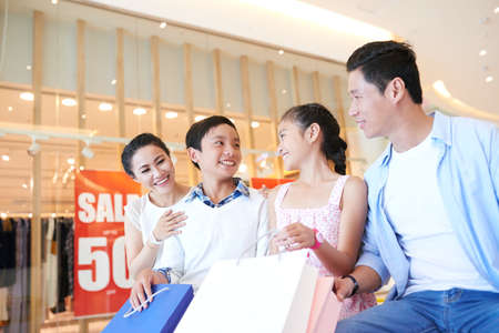 Cheerful Vietnamese family resting on bench after shopping