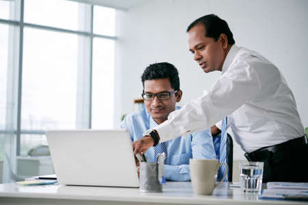 Indian business team discussing information on tablet computer Stock Photo