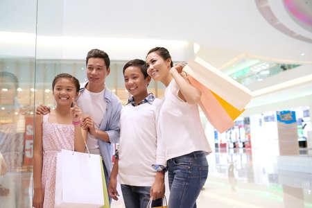Aziatische familie die voor het winkelen raam staat