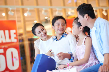 Smiling Asian boy showing his purchase to family