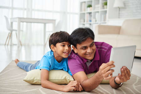 Indian father and son lying on floor and watching cartoons on digital tablet Stock Photo