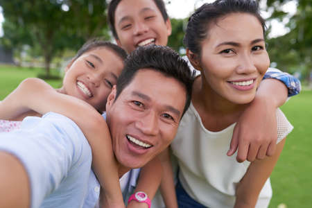 Happy Vietnamese family hugging when photographing together