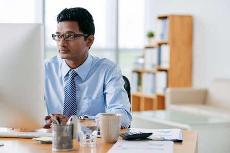 Jonge Indiase softwareontwikkelaar die op kantoor werkt Stockfoto