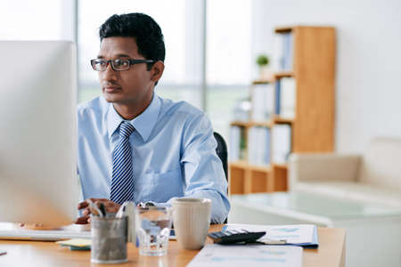 Young Indian software developer working in office Stock Photo