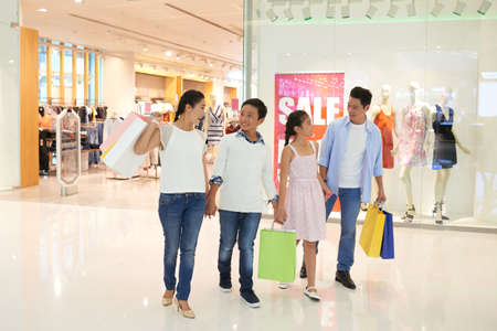 Cheerful Vietnamese family walking in shopping mall