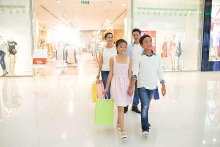 Vietnamese children and their parents walking in shopping mall together Stock Photo - 77967924