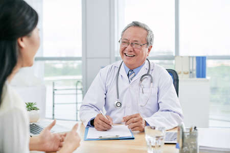 Cheerful mature doctor giving advice to female patient Stock Photo