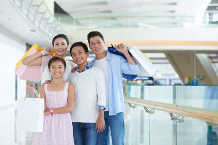 Portrait of cheerful Vietnamese family in shopping mall