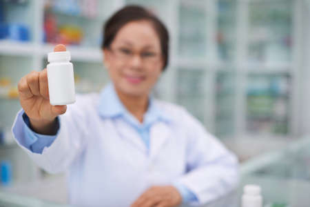 Pharmacist showing bottle with essential vitamins, selective focus