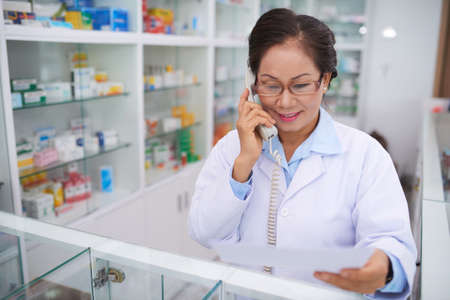 Pharmacist with document in her hands calling to medical warehouse