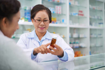 Vietnamese pharmacist reading indication and recommended dose of medication Stock Photo