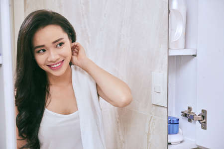 bathroom mirror: Smiling Asian woman getting ready in her bathroom