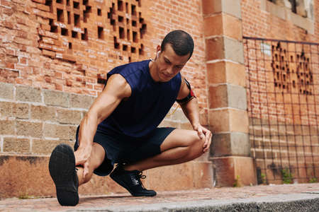 Concentrated male athlete stretching legs after jogging Stock Photo