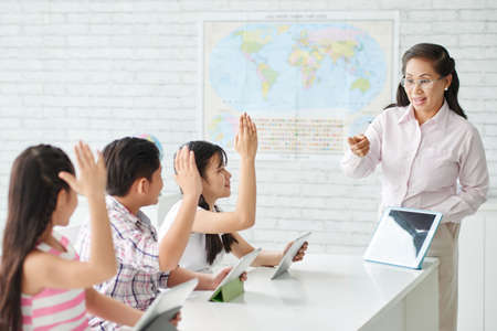 answer: Every child in class raising hands to answer a question Stock Photo