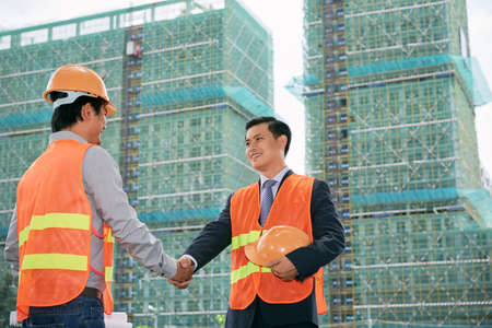 Two vietnamese construction workers greeting each other stock photo two vietnamese construction workers greeting each other stock photo picture and royalty free image image 77929076 m4hsunfo