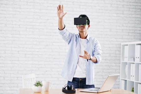 Asian man in virtual reality glasses working in office Stock Photo