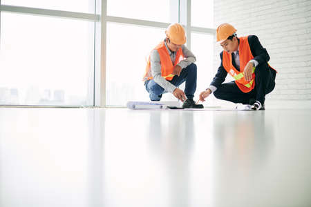Construction worker and engineer discussing plan of the building Stock Photo