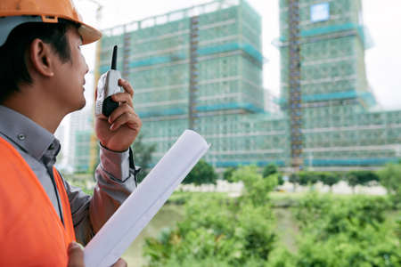 Construction worker using walkie-talkie to communicate with his team Stock Photo