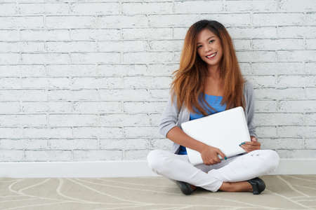 Woman with laptop sitting on floor and looking at camera