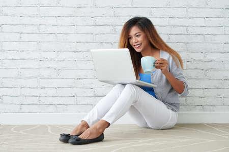 一杯のコーヒーをノート パソコンにテレビ番組を見ていると若いフィリピン人女性