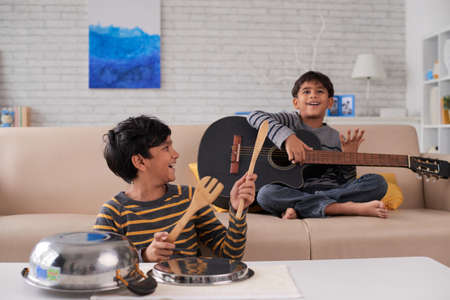 Indian kids enjoying playing instruments at home Stock Photo