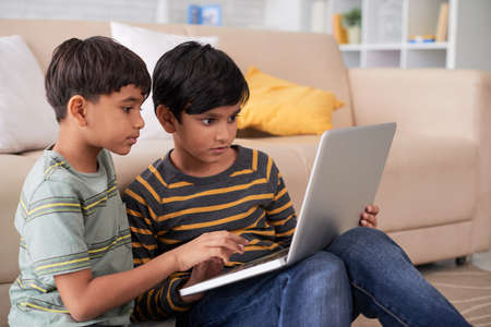 Indian kids sitting on floor and using laptop