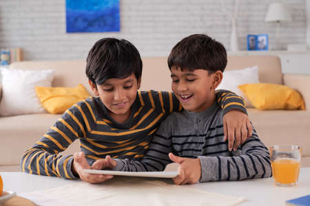 Cheerful Indian children watching something on digital tablet