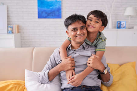 Joyful father and his smiling kid on sofa at home Stock Photo