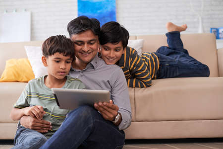Father and sons enjoying movie on digital tablet