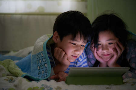 woman lying in bed: Asian brother and sister watching cartoons on digital tablet