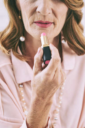 in vain: Cropped image of senior woman applying lipstick