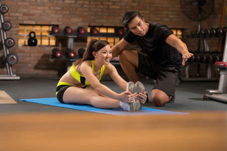 Smiling sporty girl exercising with trainer in gym Stock Photo