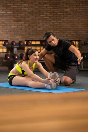 Young trainer explaining woman how to stretch Stock Photo