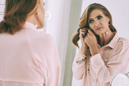 in vain: Mature woman wearing earrings in front of mirror Stock Photo