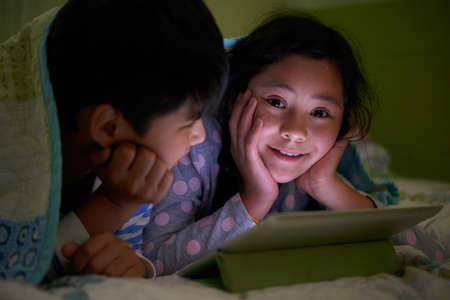 twin bed: Smiling girl enjoying watching cartoons with her brother